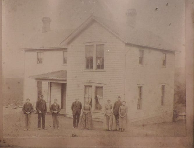 The Cummings home in Lecompton and family. Left to Right: Tom, Jim, John, Pat, Bridget, Mary, Bill, Nora.